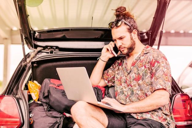 ノートパソコンと車の近くのスマートフォンを持つ男