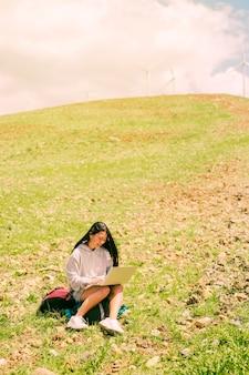 バックパックの上に座って、緑の丘の上のラップトップで働く女