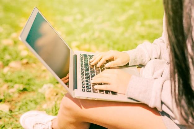 緑の芝生の上に座っているとラップトップで働く女性