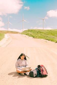 道路の真ん中に座っているとラップトップに取り組んでいる女性