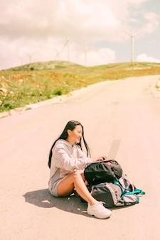 道路上に座っているとバックパックに置かれたラップトップに取り組んでいる女性