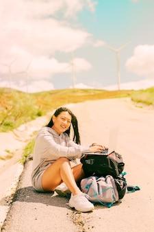 Женщина сидит на обочине дороги и работает на ноутбуке на рюкзаках