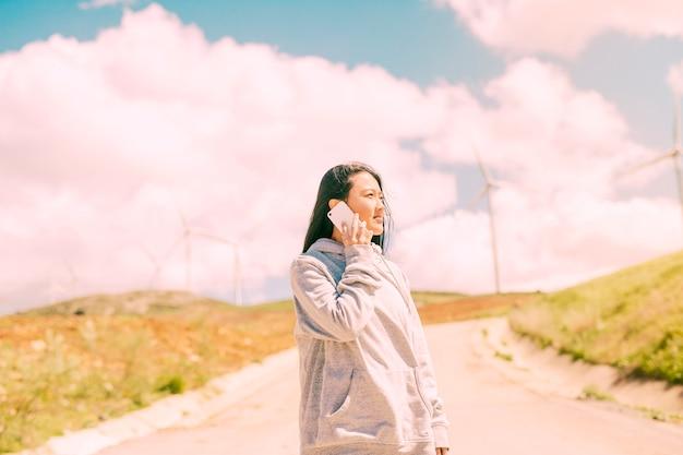 アジアの女性が国の風景に電話をかける