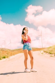 スタイリッシュな女性が田舎道に電話をかける