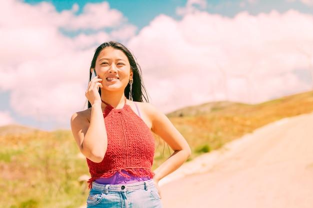 笑顔の女性が田舎で電話をかける
