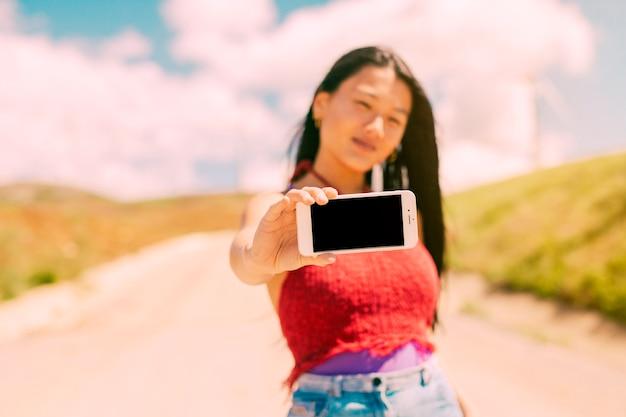 アジアの女性の空白の画面を持つスマートフォンを表示