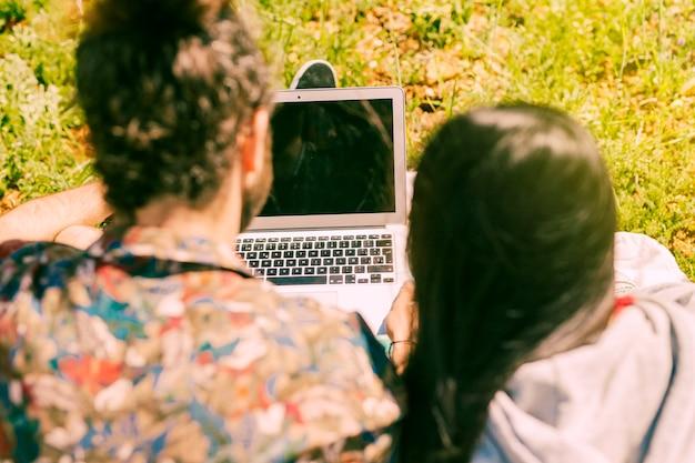 Молодая пара с ноутбуком на поляне