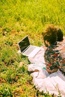 フィールドでノートパソコンを見ているカップル
