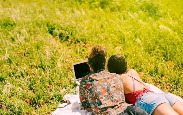 牧草地でノートパソコンを探しているカップル