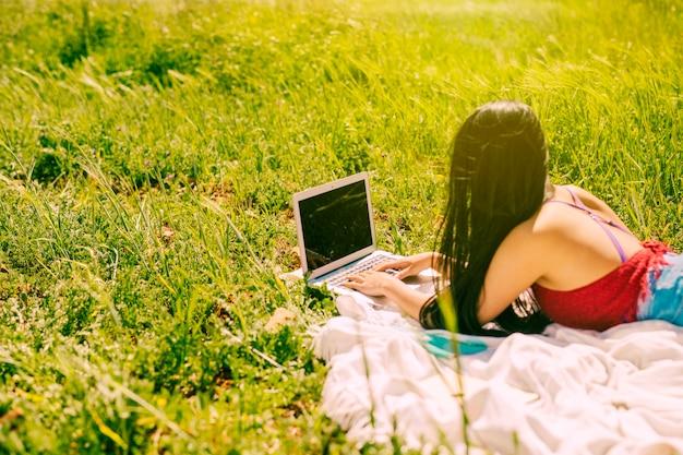 草原のラップトップに取り組んでいる若い女性