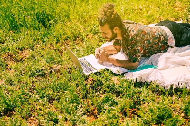戸外でノートパソコンを見て若い男性