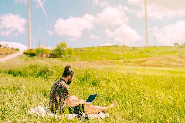 Молодой брюнет мужчина сидит с ноутбуком в сельской местности