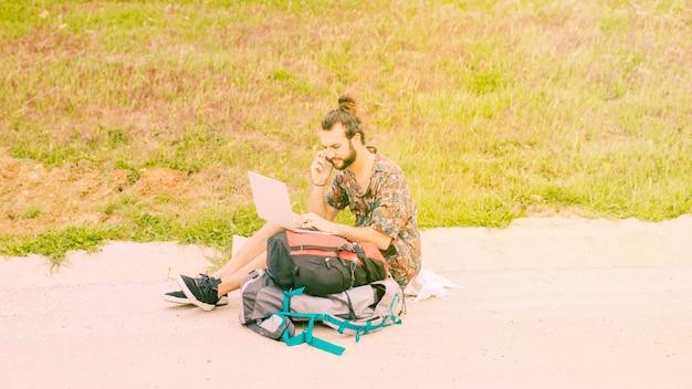 若い男性のラップトップでサーフィンをして田舎で電話で話しています。