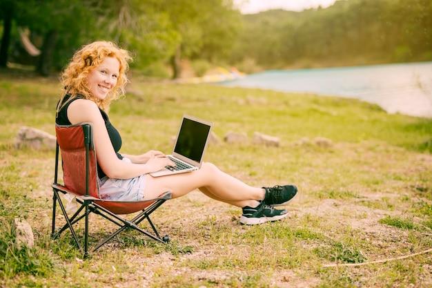 屋外のラップトップに取り組んでいる笑顔の女性