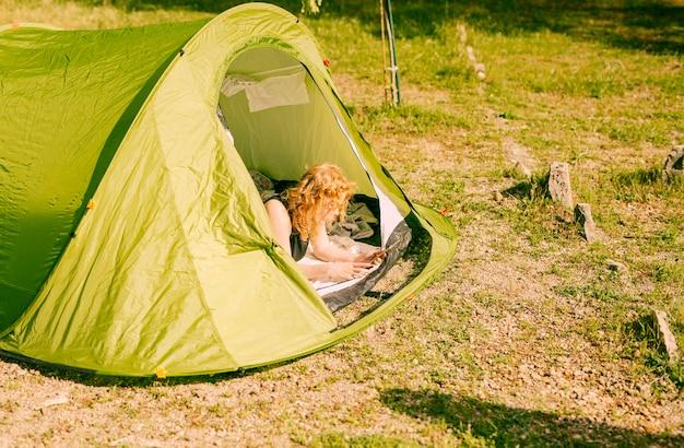 タブレットとテントの中で横になっている女性