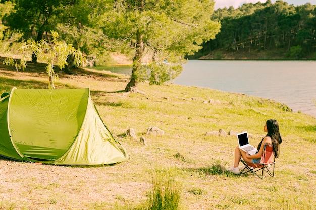 Женщина с ноутбуком сидит возле палатки