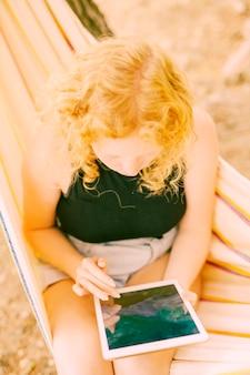 タブレットを屋外でサーフィンの女性