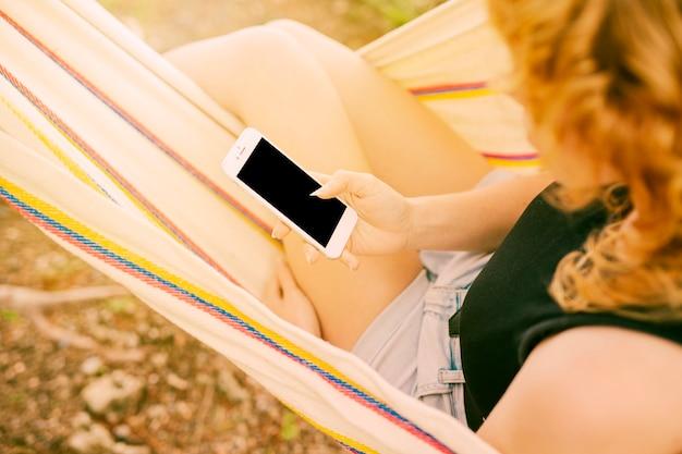 女性のハンモックでスマートフォンを使用して