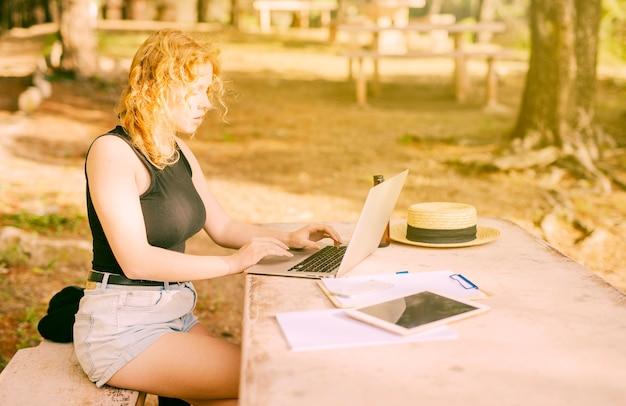 若い女性が公園でラップトップ上でインターネットを閲覧