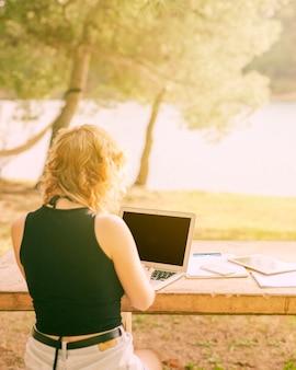 顔の見えない女性に座っていると絵のような場所でラップトップに取り組んで