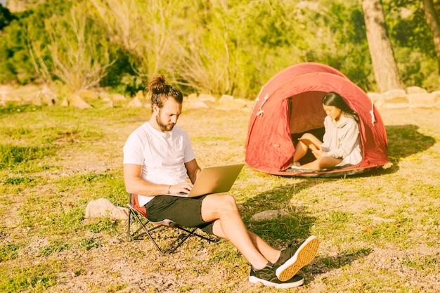 カップルがキャンプで休んでいるとリモート作業