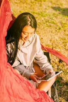 テントの中で座っているタブレットを持つ女性旅行者