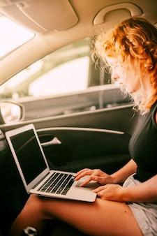 女性が車の中に座っているとラップトップを使用して