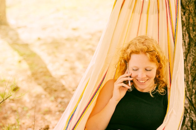 ハンモックで電話で話す笑顔の女性