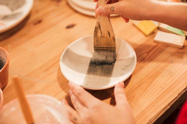 木製の机の上の絵筆を持つ女性手絵画セラミックスプレートのクローズアップ