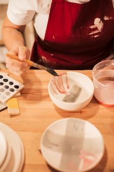 セラミックボウルを塗る女性の陶工の立面図