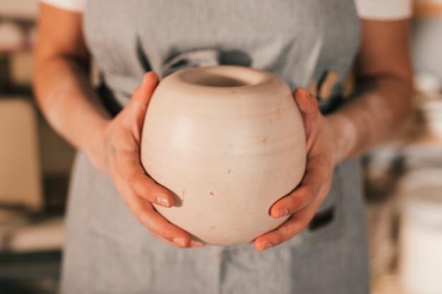 手作りの鍋を持っている女性の陶工の手の中央部