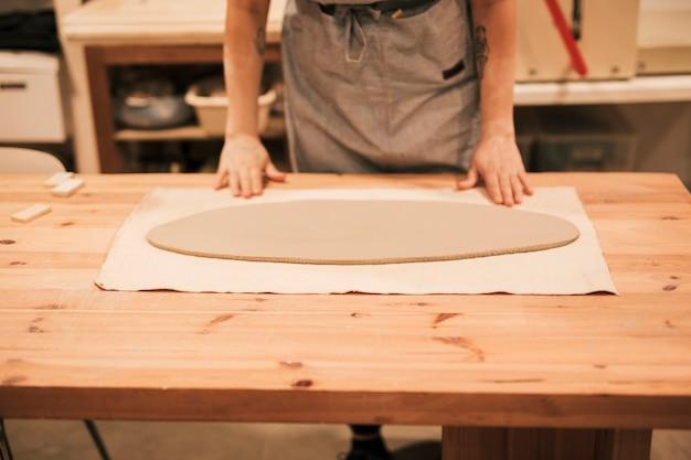 Крупный план женского гончара с овальной формы сплющить глину на деревянный стол