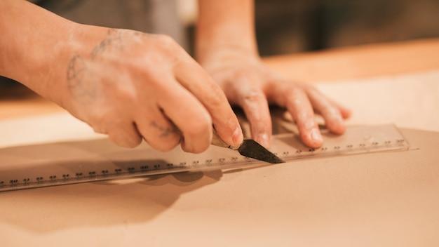 定規とツールで粘土を切る女性の陶工の手のクローズアップ
