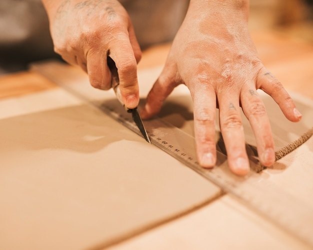 女性の陶工の手が鋭い道具で粘土を切る
