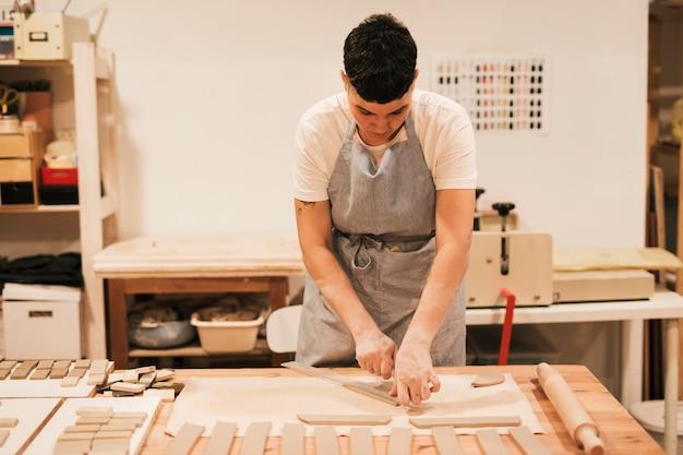 長方形の粘土を切る女性の陶工