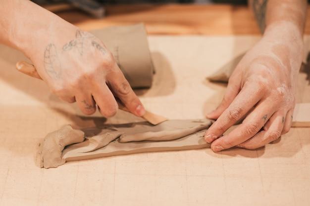 木製の道具で湿った粘土を成形する女性の陶工の手のクローズアップ