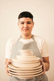 Портрет улыбающегося женского гончара, держащего стопку посуды в руке на бежевом фоне