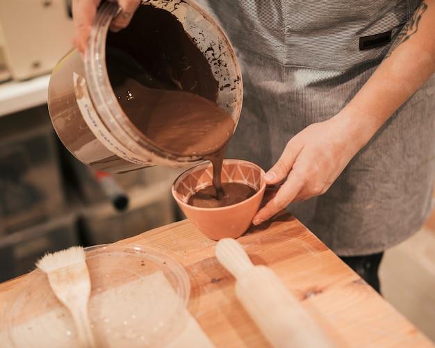 木製のテーブルの上にボウルに茶色の塗料を注ぐ女性の陶工の手のクローズアップ