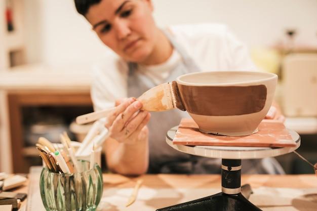 女性の陶工のペイントブラシで粘土ボウルを塗る