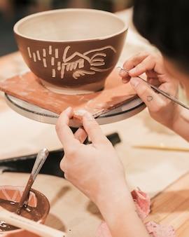 ボウルに彫刻女性の陶工の手のクローズアップ