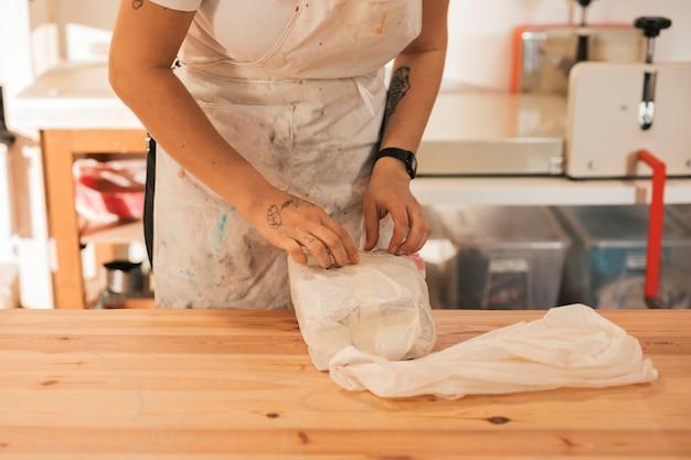 ワークショップで粘土を開ける女性陶芸家
