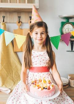 誕生日ケーキを持つ少女の笑顔