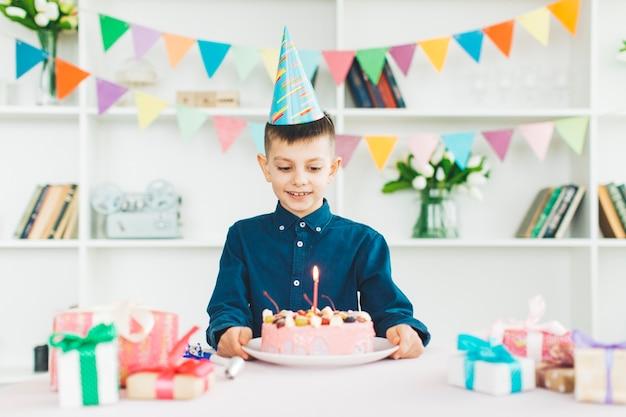 誕生日ケーキを持つ少年の笑顔