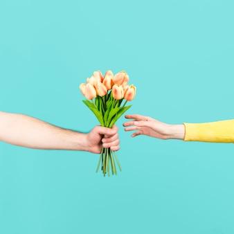 花のブーケを提供する手