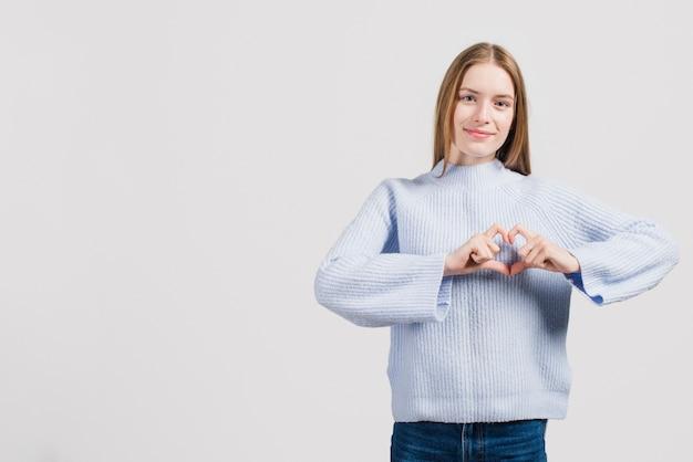 Девушка делает сердце руками