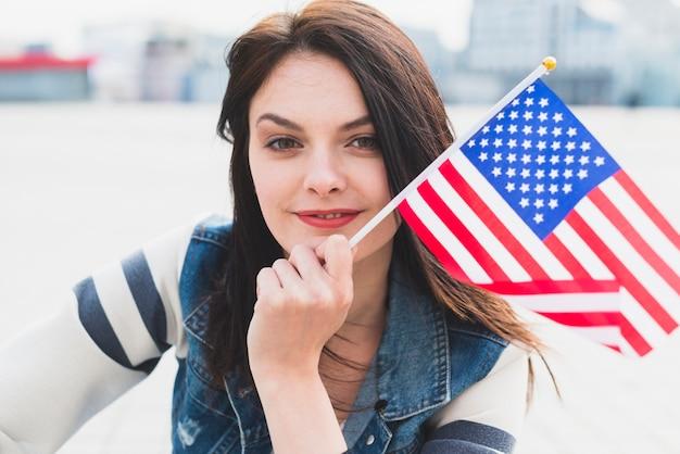 笑顔とアメリカの国旗を手で保持している女性