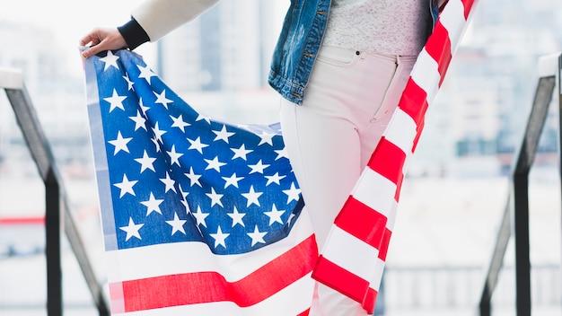 足の後ろにアメリカの国旗を保持しているスリムな女性
