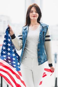 大きなアメリカ国旗と一緒に歩いている誇りに思っている女性