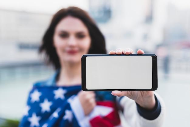 空白の画面を持つ若い女性示すスマートフォン