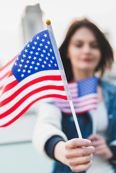 Молодая женщина держит американские флаги